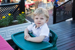 Portrait of beautiful little toddler boy sitting in outdoor rest Royalty Free Stock Images