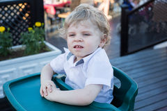 Portrait of beautiful little toddler boy sitting in outdoor rest Royalty Free Stock Photo