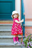 Portrait of beautiful little toddler girl in pink summer look clothes, fashion dress, knee socks and hat. Happy healthy. Baby child posing infront of colorful royalty free stock images