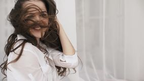 Portrait of a beautiful long-haired brunette with hair developing on a wind isolated on a gray background. stock video