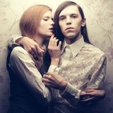 Portrait of beautiful long haired people in vintage style: hands. Ome boy with brown hair and whispering gorgeous red-haired girl posing together. Studio shot Royalty Free Stock Image