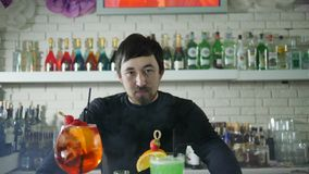 Portrait of beautiful male beside vivid alcohol drinks with berries at counter in bar interior with bottles in white. Portrait of beautiful male beside vivid stock video