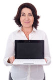 Portrait of beautiful mature business woman showing laptop with. Blank screen isolated on white background Stock Photography