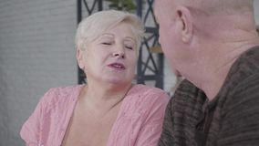 Portrait of beautiful mature caucasian woman with brown eyes talking emotionally to bald husband. Attractive retiree