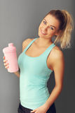 Portrait of beautiful mature woman with bottle smiling in health club Royalty Free Stock Image
