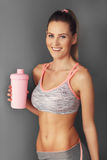 Portrait of beautiful mature woman with bottle smiling in health club Stock Photos