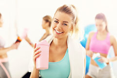 Portrait of beautiful mature woman with bottle smiling in health club royalty free stock photos