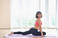 Portrait of a beautiful mature woman siting in yoga pose at the gym Royalty Free Stock Photo