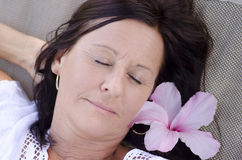 Sleeping mature woman with flower Royalty Free Stock Images
