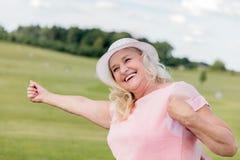 Beautiful mature woman dancing in the field. Stock Image