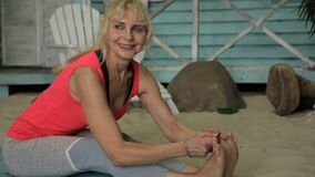 Portrait of beautiful mature woman, who is doing seated forward bend outside. Lady is having a yoga training on the sandy beach near her blue house, stretching stock video