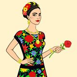 Portrait of the beautiful Mexican woman in a festive dress with a rose in a hand. Royalty Free Stock Image