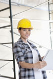 Portrait of beautiful mid adult architect wearing hardhat with blueprints Royalty Free Stock Photography
