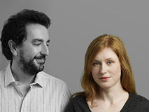 Portrait of beautiful mid-adult woman with man looking at her against gray background Royalty Free Stock Photography