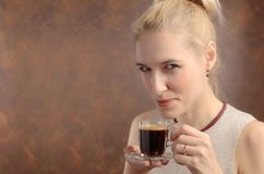 Portrait of a beautiful mid age woman with cup of coffee. Attractive and happy blonde blowing on hot coffee. Copy space royalty free stock photos