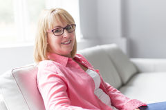 Portrait of beautiful middle age mature senior woman posing on a sofa at home. A portrait of beautiful middle age mature senior woman posing on a sofa at home Stock Photography