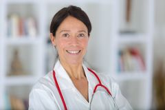 Portrait beautiful middle aged female doctor smiling Stock Photo