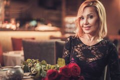 Portrait of beautiful middle aged woman with bouquet of red roses in restaurant Royalty Free Stock Photography