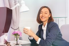 Beautiful businesswoman drinking coffee in office royalty free stock photos