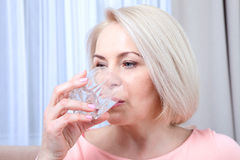 Portrait beautiful middle aged woman drinking water in the morning. Woman's face close up Royalty Free Stock Photography
