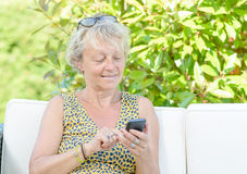 Portrait of a beautiful middle-aged woman on phone outside Stock Photography