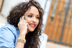Beautiful mixed woman in urban background on the phone Royalty Free Stock Photos