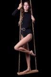 Portrait of beautiful model posing on rope swing in body dress Stock Photos