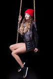 Portrait of beautiful model in red hat and jacket posing on rope Stock Image