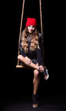 Portrait of beautiful model in red hat and jacket posing on rope Stock Photos
