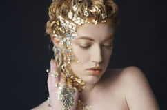 Portrait of beautiful model with shiny foil on face and hair stock photography
