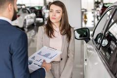 Beautiful Woman Choosing Car in Showroom stock images
