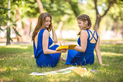 Portrait of a beautiful, modern and young girls in modern dresses in a park. Fashionable and charming young girls with books. royalty free stock photography