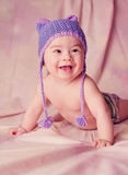 Portrait of a beautiful 6 months baby smiling dressed in funny knitted hat Stock Image