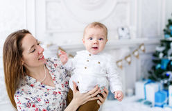 Portrait of beautiful mother and baby son near the Christmas tree Royalty Free Stock Photo