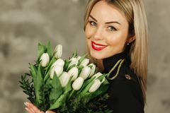 Portrait of beautiful mother hold a bouquet of white tulips on 8th of march. Flowers in woman`s hand. Blond hair mom royalty free stock photography