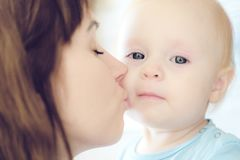 Portrait of beautiful mother kissing her child girl royalty free stock photo