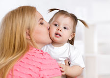 Portrait of beautiful mother kissing her child. Girl indoor Royalty Free Stock Photography