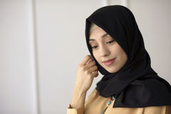 Portrait of a beautiful Muslim girl in a black scarf on his head on a light classical background Royalty Free Stock Image