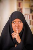 Portrait of a beautiful muslim girl wearing a hijab, and doing a silence sign with her hand, in a blurred background.  Stock Photography