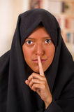 Portrait of a beautiful muslim girl wearing a hijab, and doing a silence sign with her hand, in a blurred background.  Royalty Free Stock Image