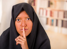 Portrait of a beautiful muslim girl wearing a hijab, and doing a silence sign with her hand, in a blurred background.  Stock Images