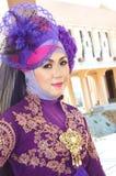 Portrait of a beautiful muslim woman. Wearing a purple moslem wear modification Royalty Free Stock Images