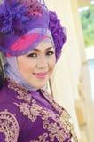 Portrait of a beautiful muslim woman. Wearing a purple moslem wear modification Stock Photos