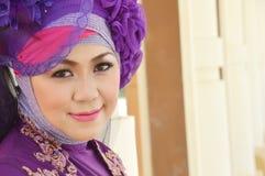 Portrait of a beautiful muslim woman. Wearing a purple moslem wear modification Royalty Free Stock Photo