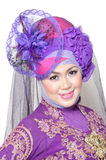 Portrait of a beautiful muslim woman. Wearing a purple moslem wear modification on white background Stock Photos