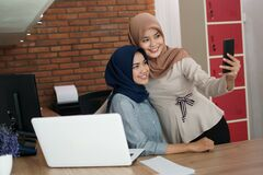 A portrait of a beautiful Muslim woman who is very happy with her partner and selfie while working