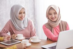 Beautiful muslim women explaining project on laptop to her partn. Portrait of beautiful muslim women explaining project on laptop to her partner at coffee shop Royalty Free Stock Photo