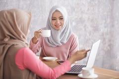 Beautiful muslim women explaining project on laptop to her sibli. Portrait of beautiful muslim women explaining project on laptop to her sibling at coffee shop Stock Photos