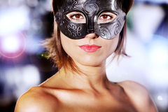 Portrait of beautiful and mysterious woman with carnival mask. With city lights background Stock Photography