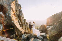 Portrait of beautiful newlywed couple in bright sunset lights on majestic mountain landscape with big rocks as backround.  royalty free stock photography